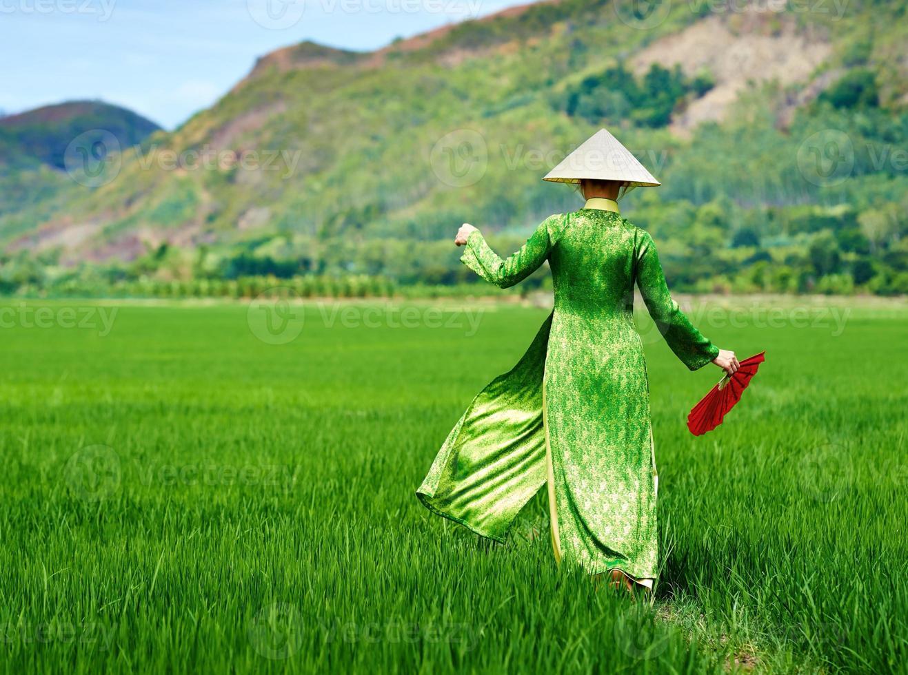 womanl promenader i en traditionell lång klänning för risfält foto