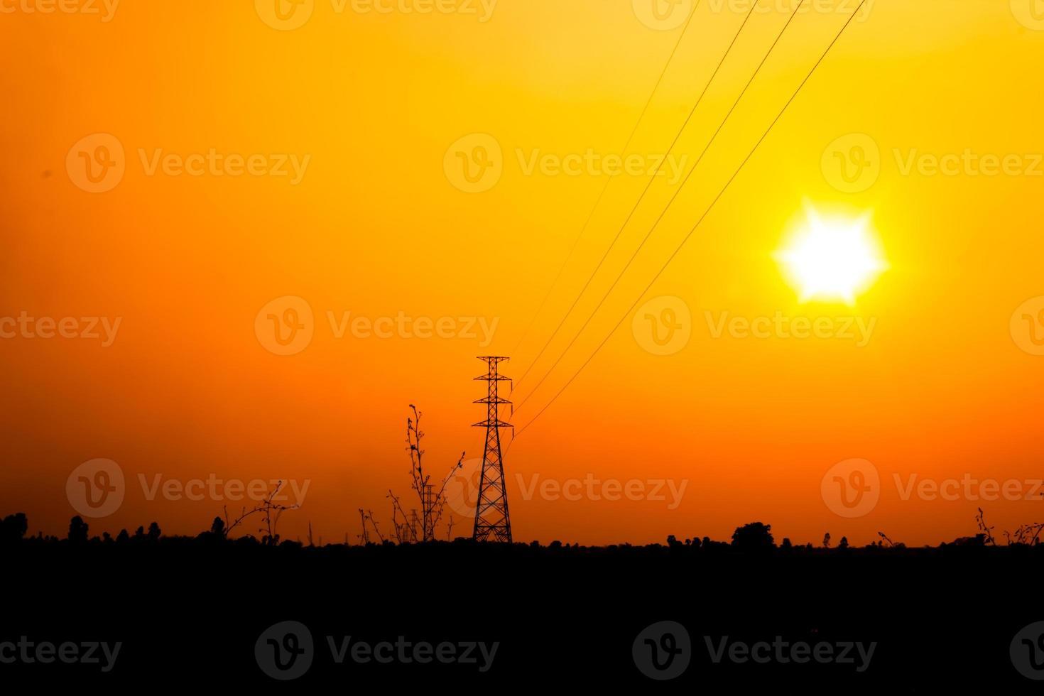 högspänningspol med orange himmel foto