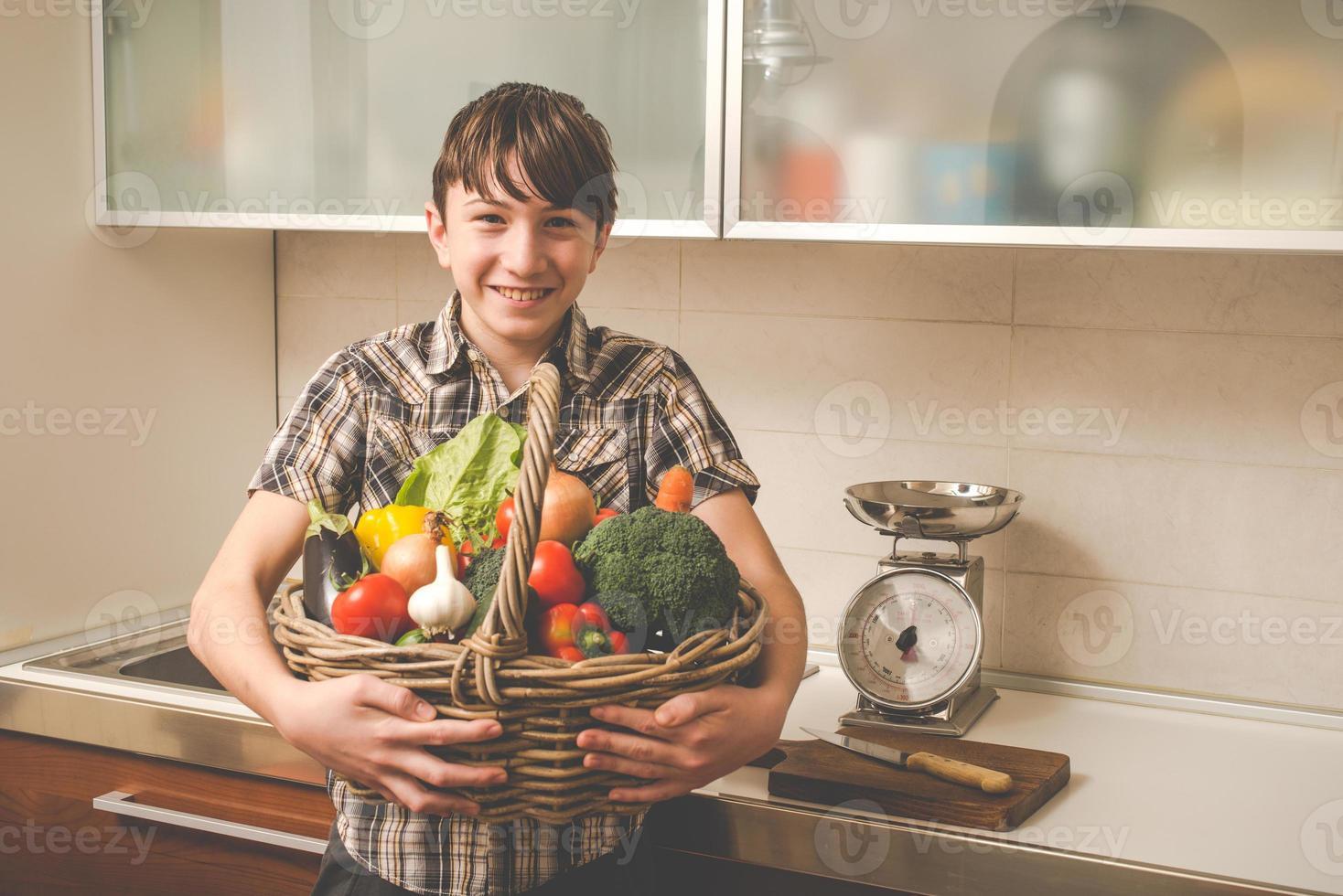 pojke förbereder grönsaker i köket - vegetariska friska människor foto
