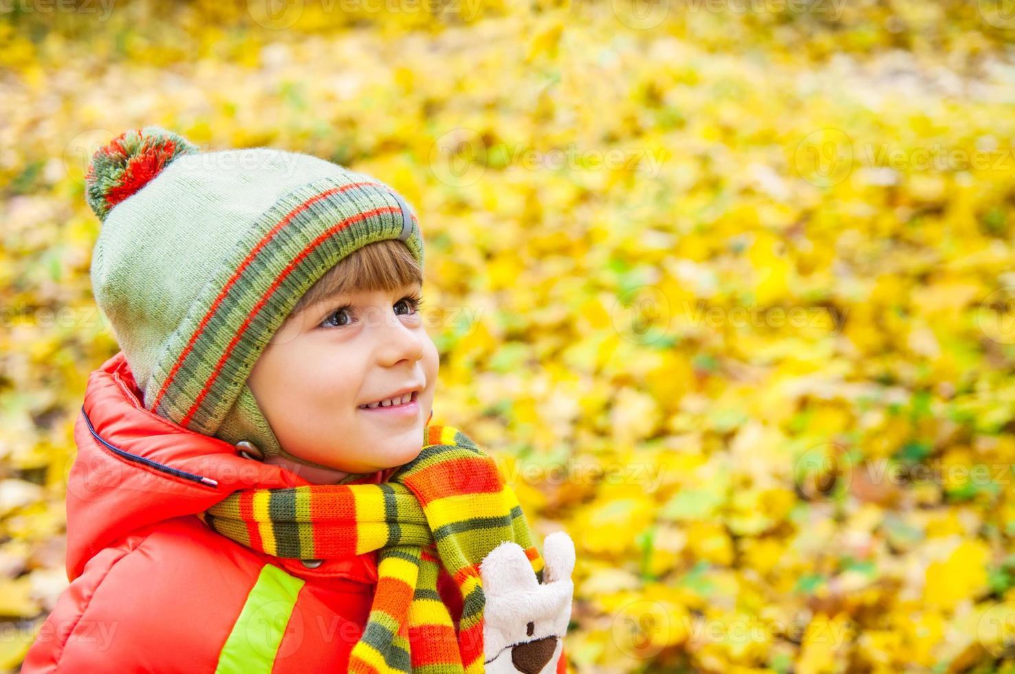 lycklig pojke som ler i höstparken foto