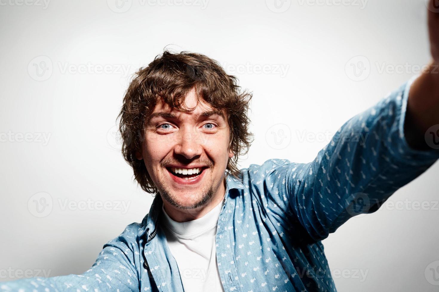 närbild porträtt av en ung glad man innehar smartphone foto