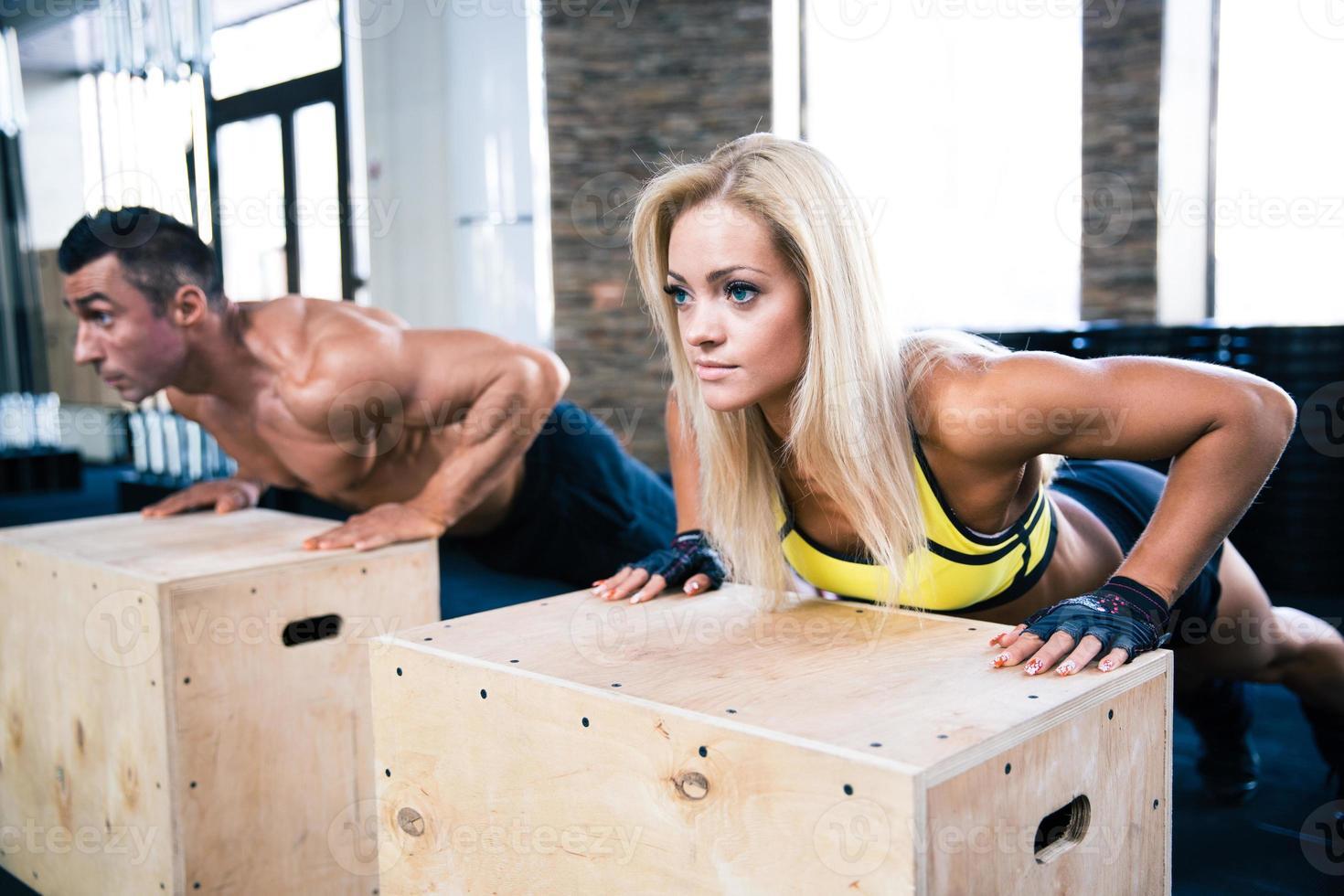 kvinna och man gör armhävningar på gymmet foto