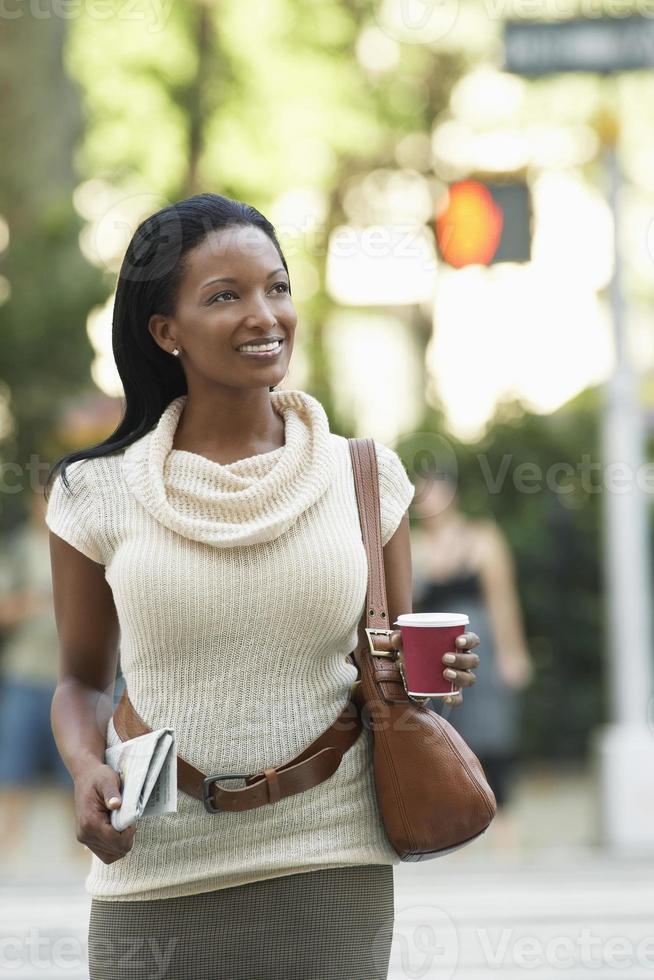 kvinna med tidning och kaffekopp på gatan foto