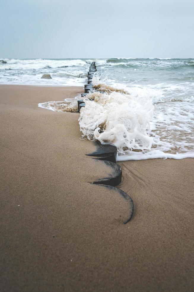 vågor kraschar i groyne på det baltiska havet foto