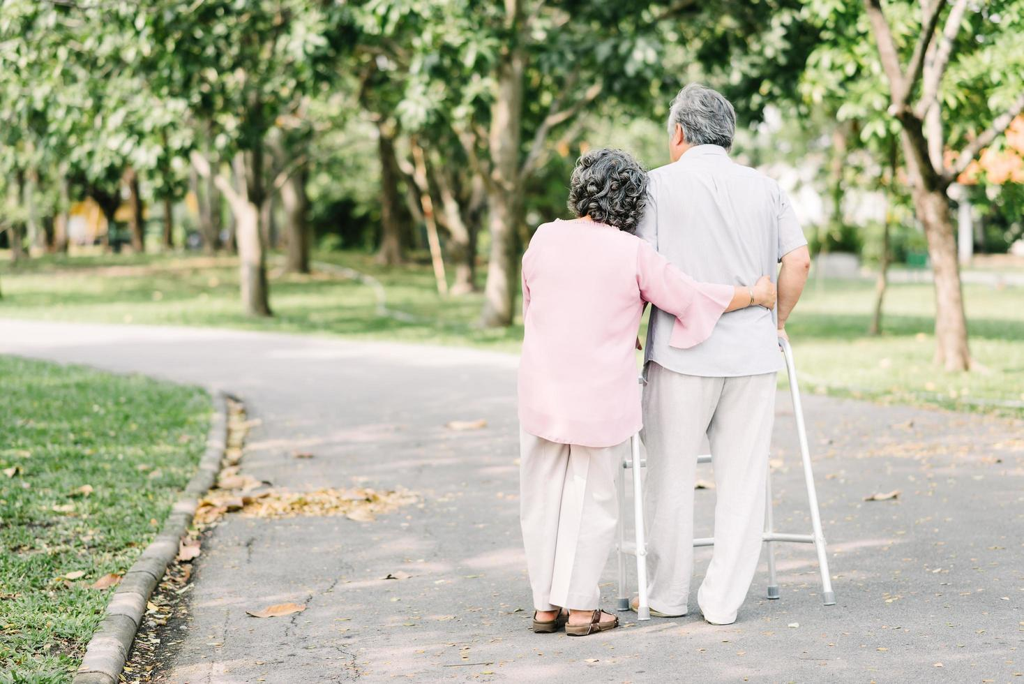äldre par som omfamnar i parken foto