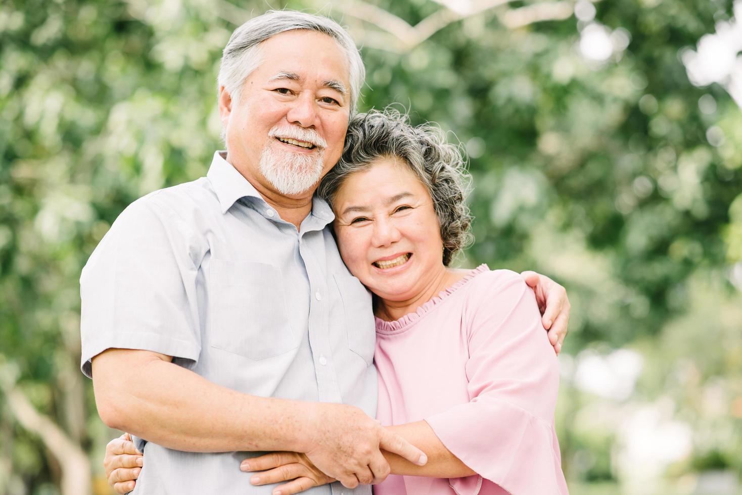äldre par som omfamnar i utomhusparken foto