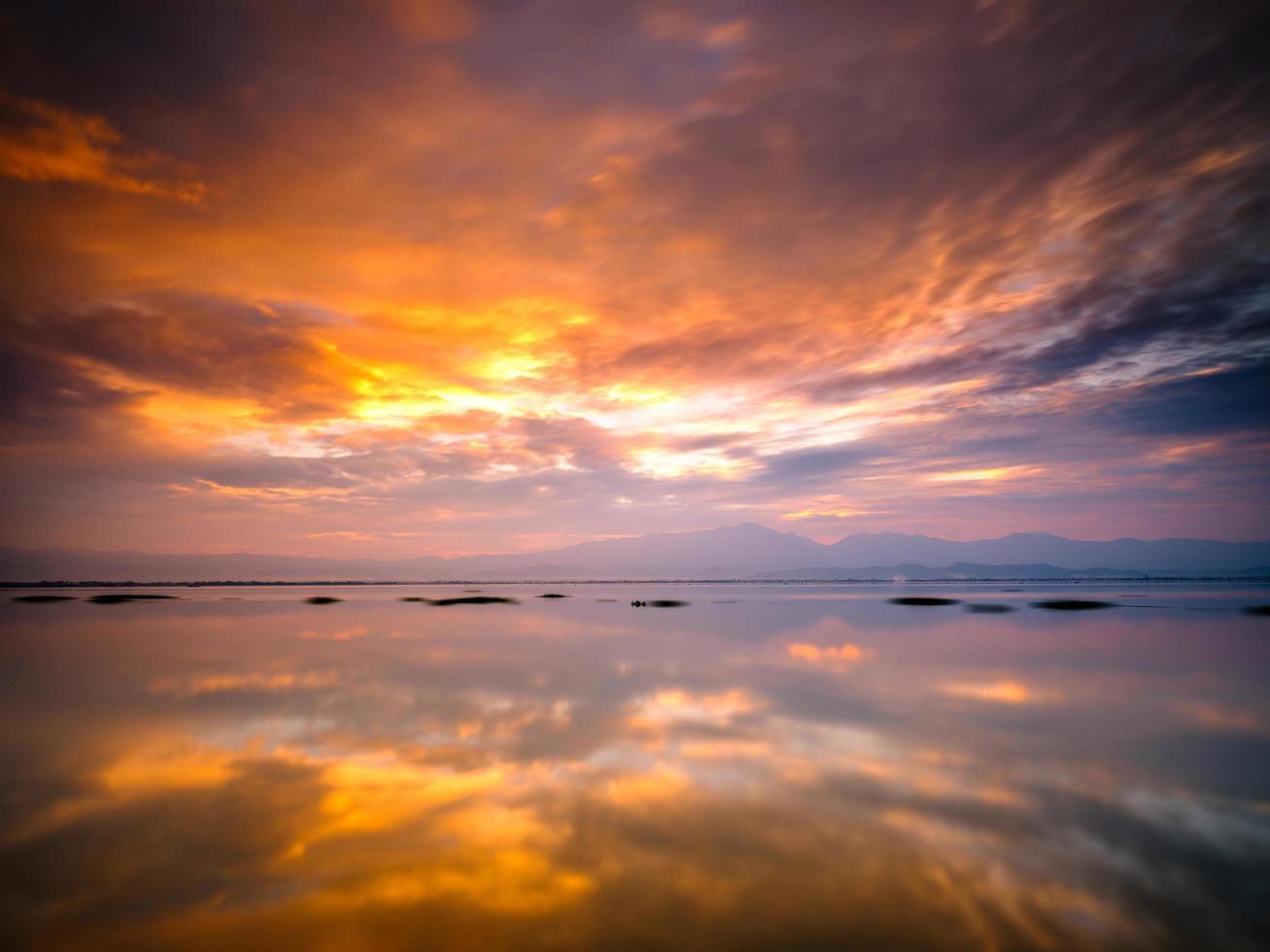 solnedgång reflekterande i stillastående vatten foto