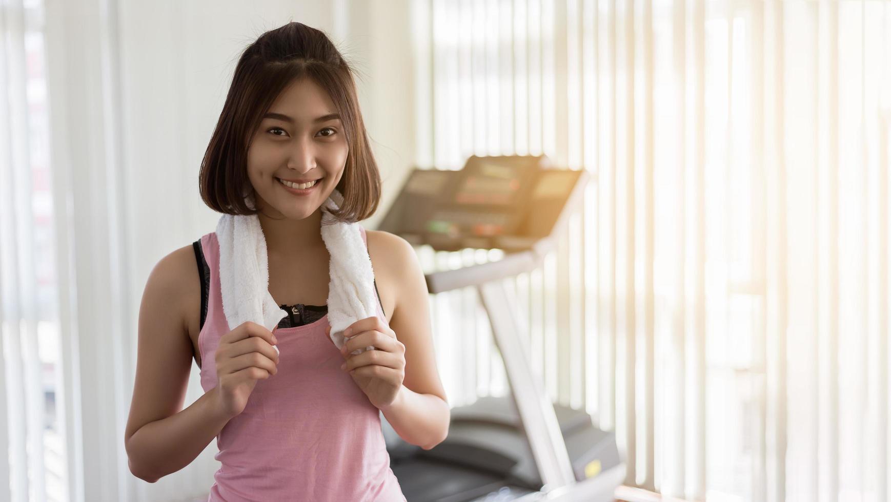 kvinna framför löpbandet på gymmet foto