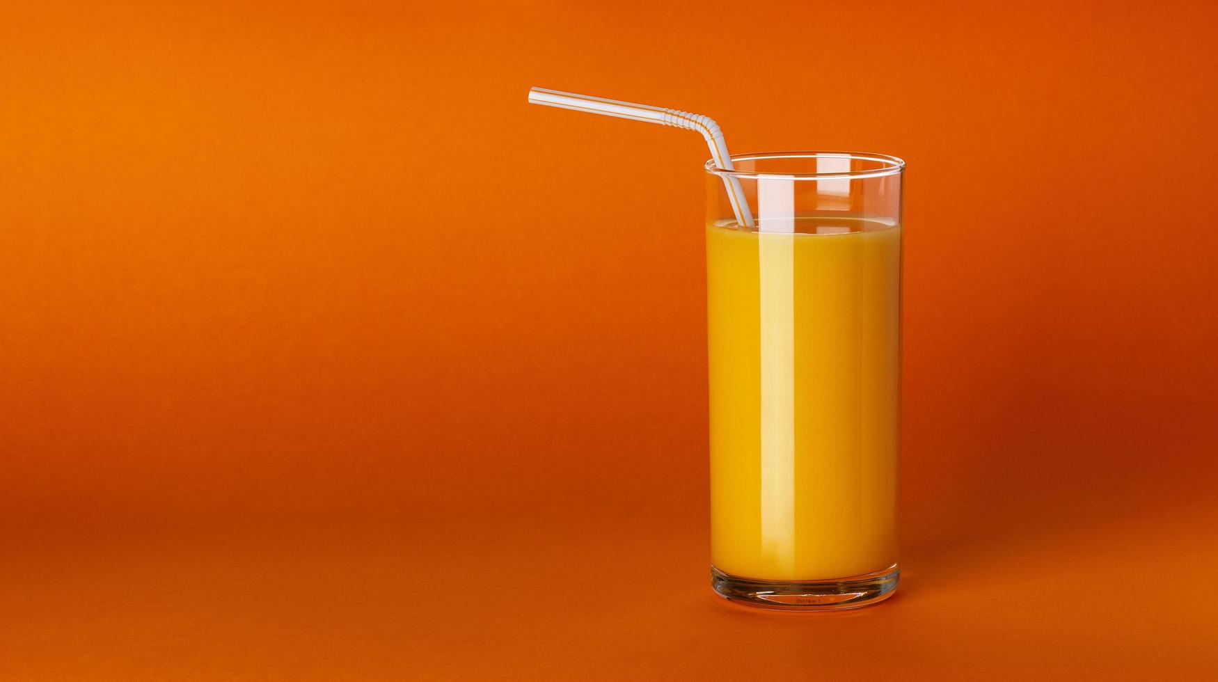 ett glas apelsinjuice på orange bakgrund med kopieringsutrymme foto