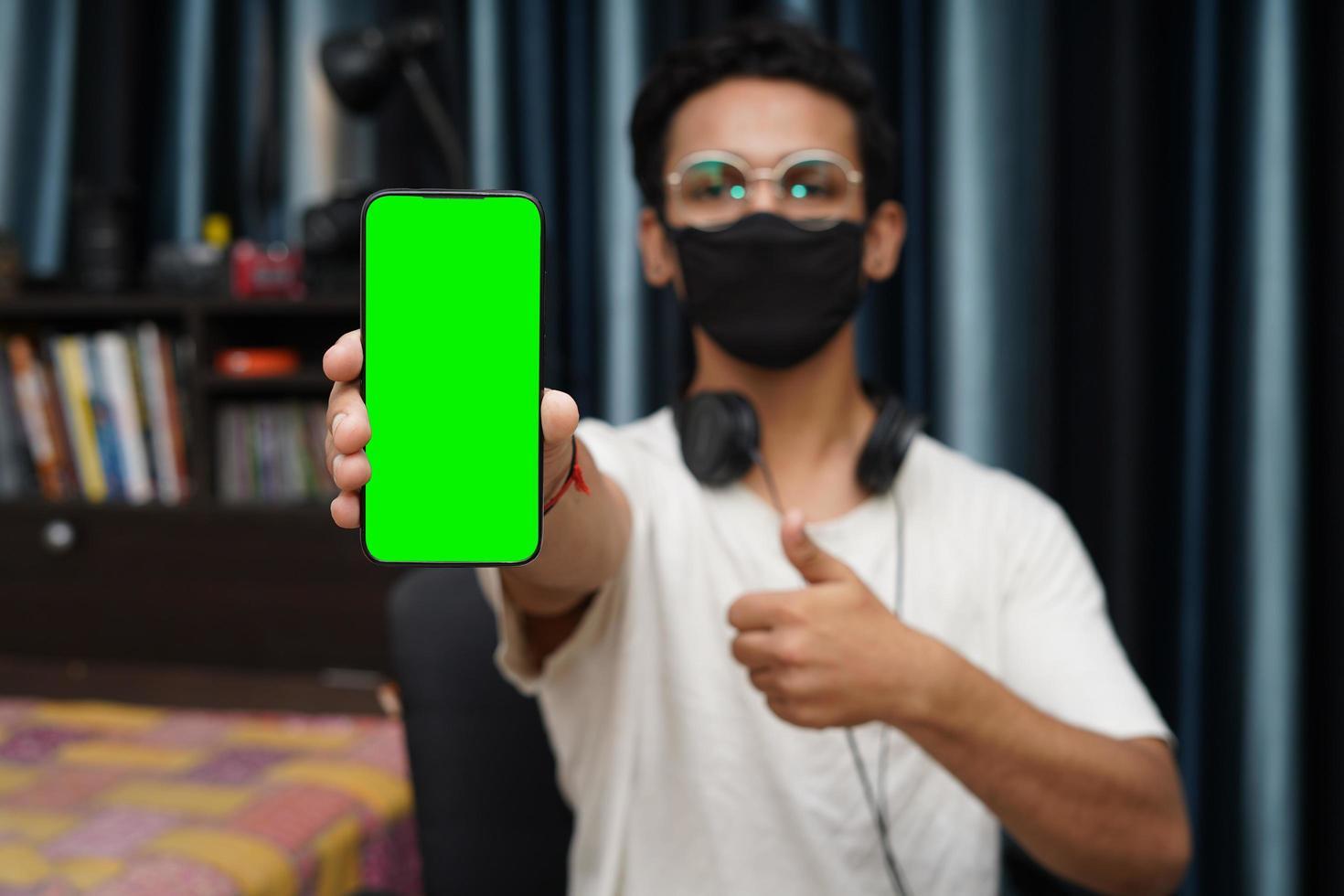 ung indisk pojke som håller en telefon med grön skärm foto