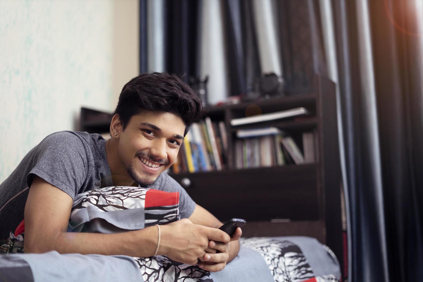 ung indisk pojke som använder sin telefon som ligger på sin säng foto