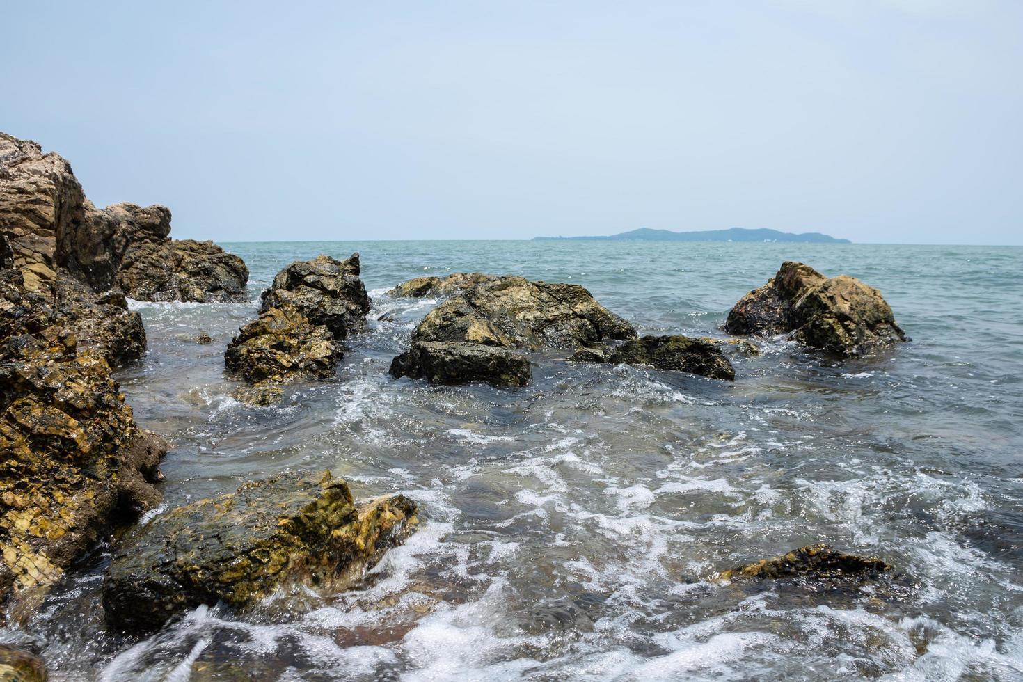 vågor kraschar i stenar foto