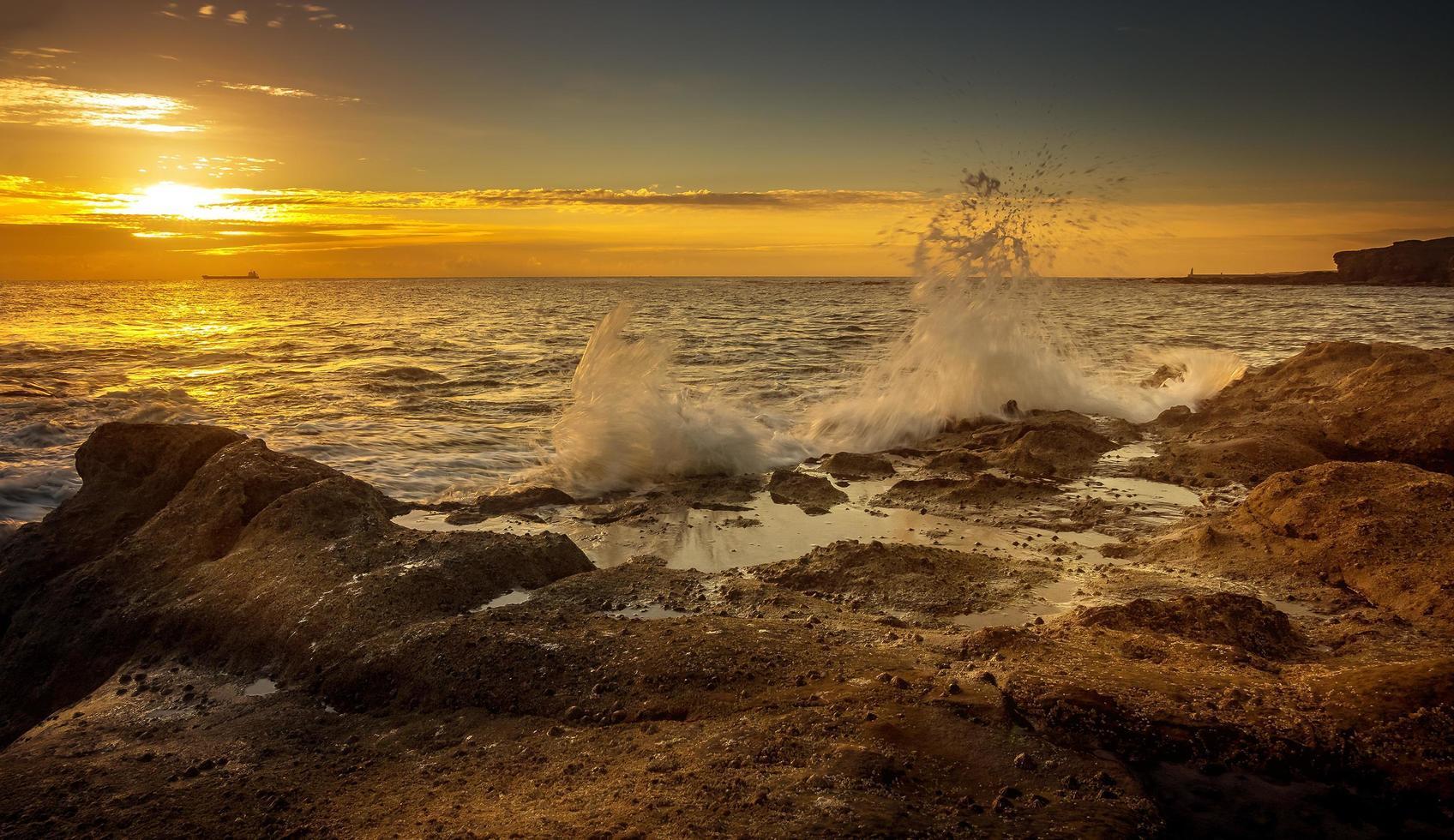 havsvågor kraschar på stenig strand foto