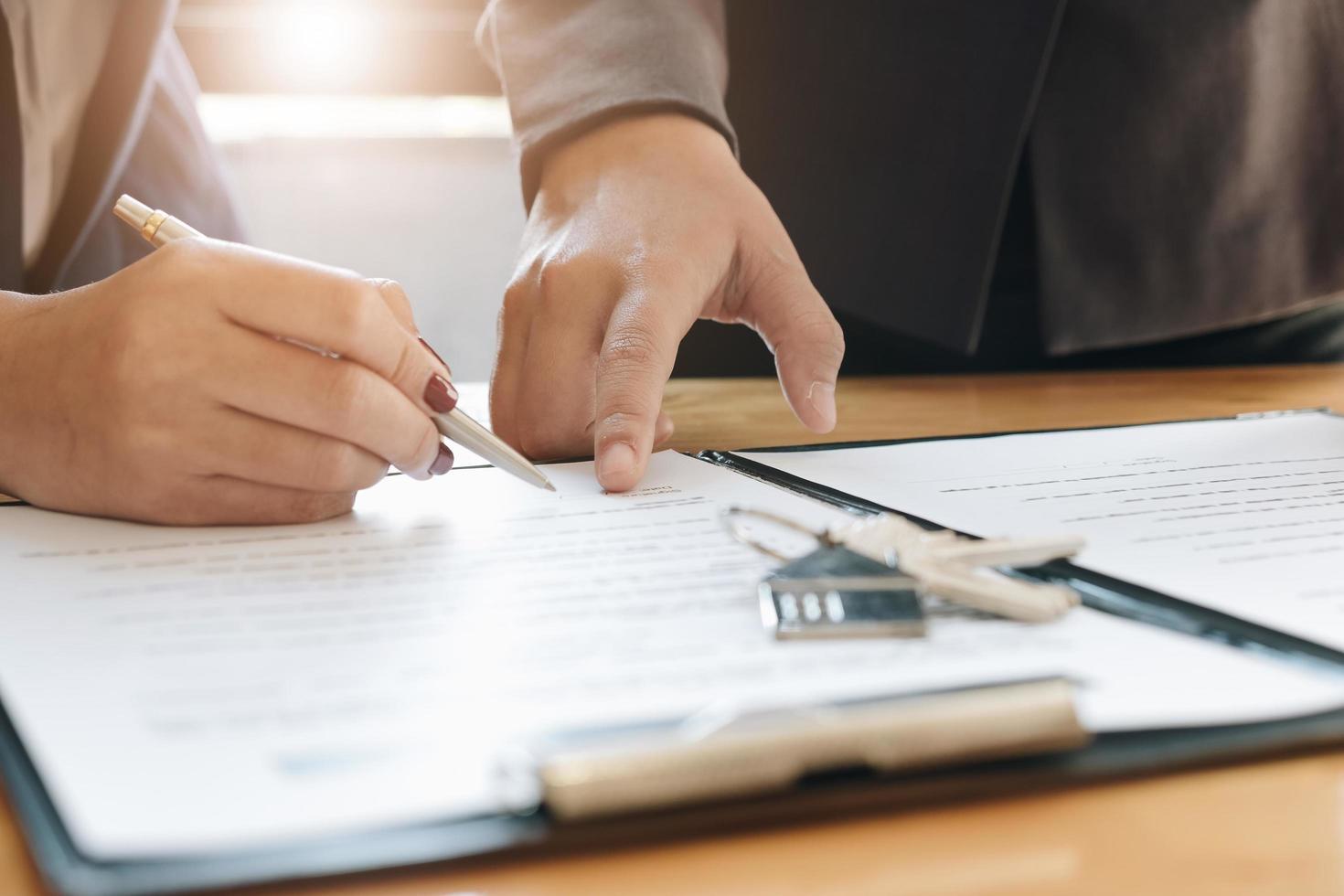 fastighetsmäklare som visar klienten var han ska underteckna foto