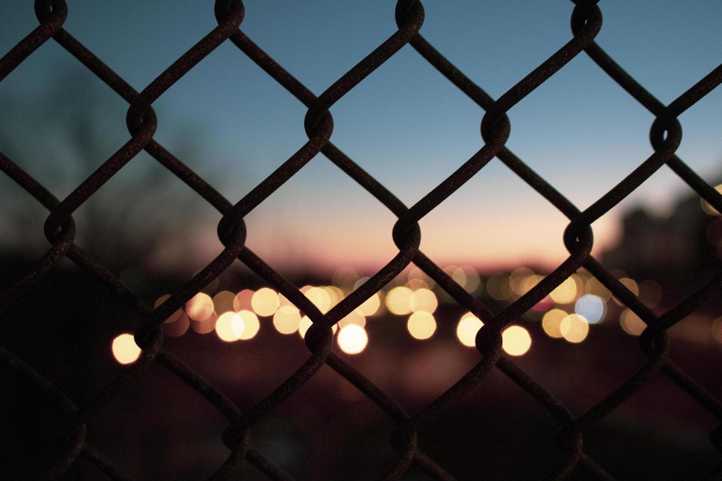 silhuett av staket och stadsljus, ur fokus foto