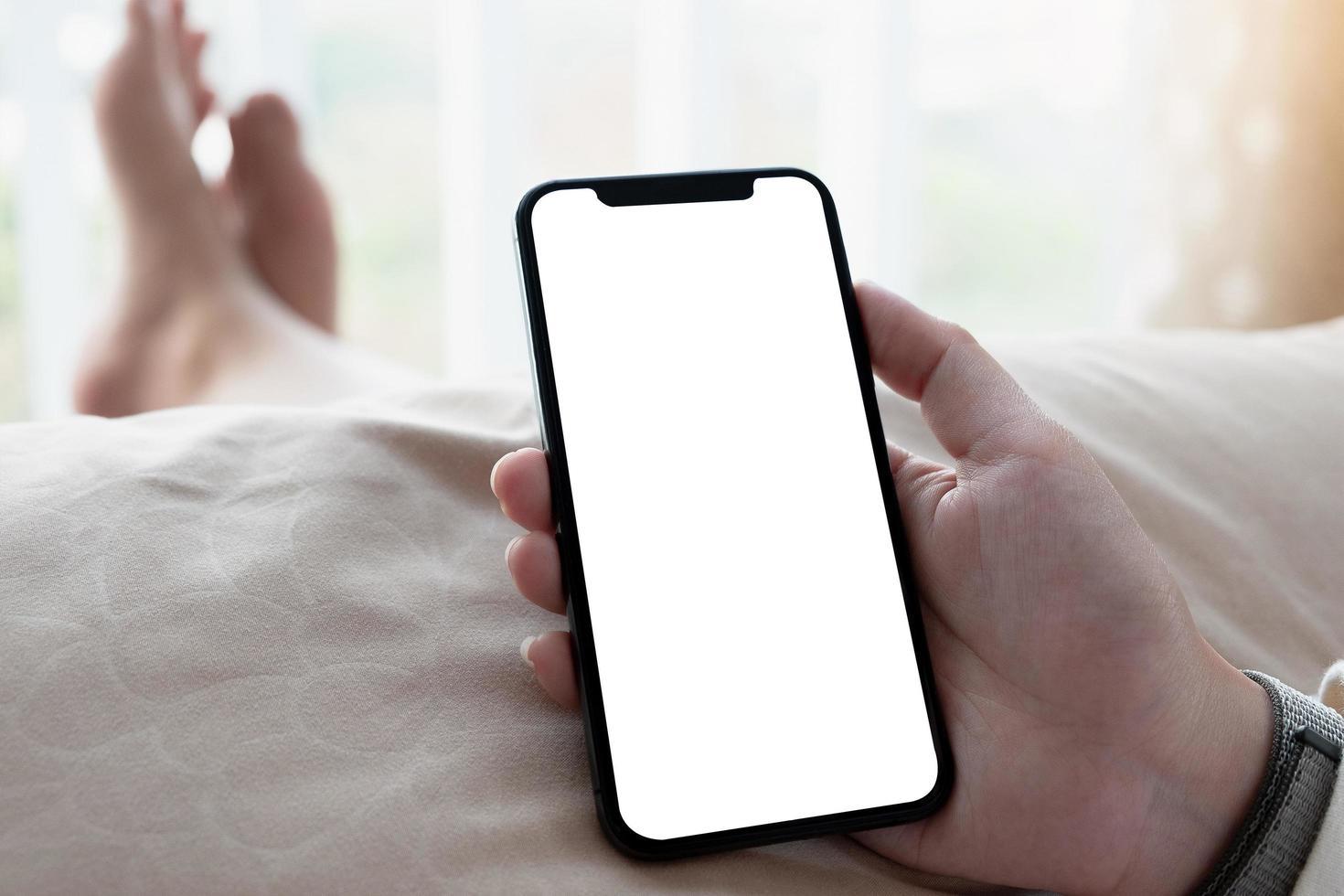 närbild av personen som rymmer telefonen i sängen foto