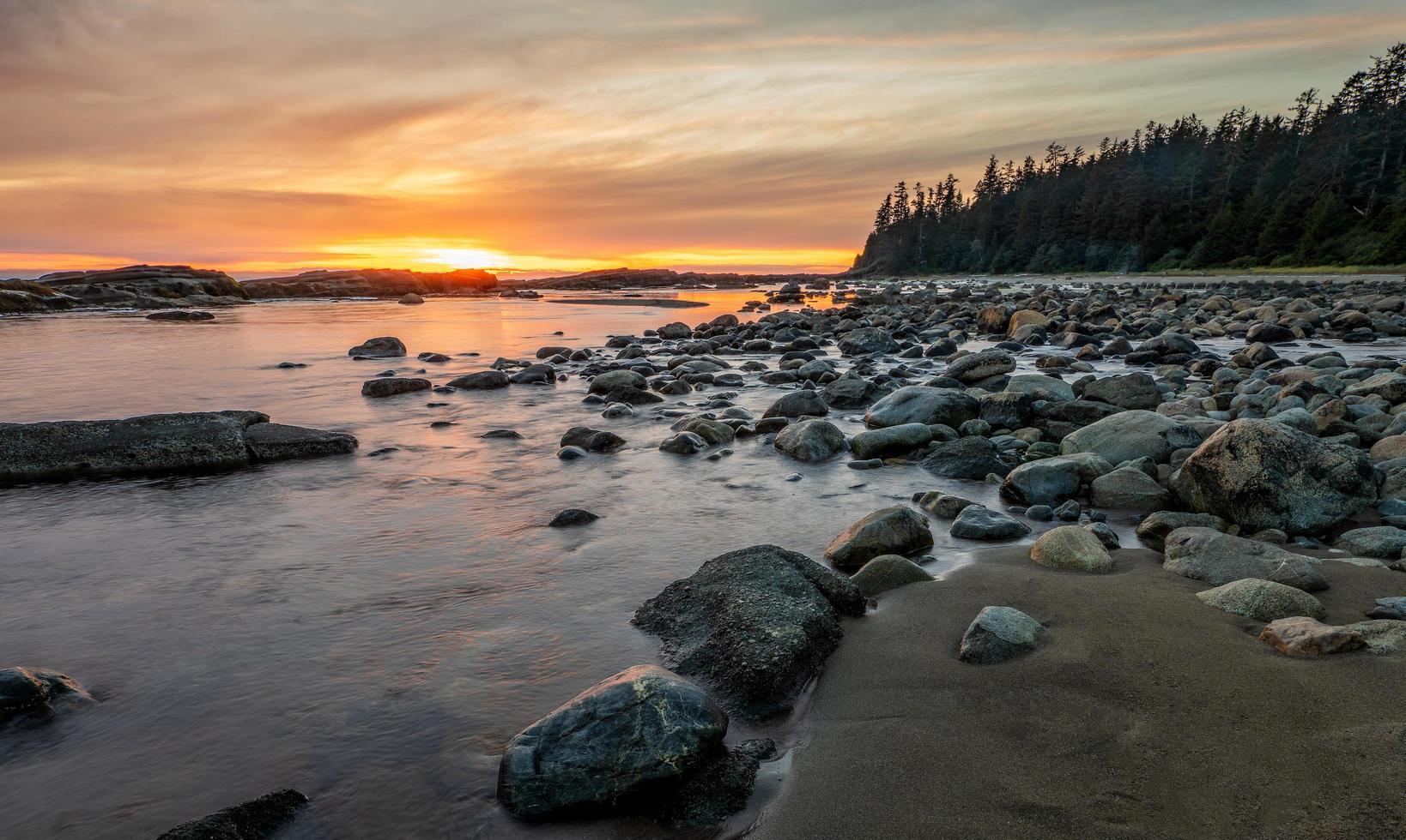 stenig strand under solnedgången foto