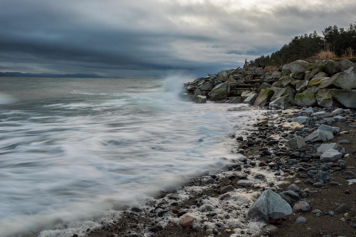 stenig strand under molnig himmel foto