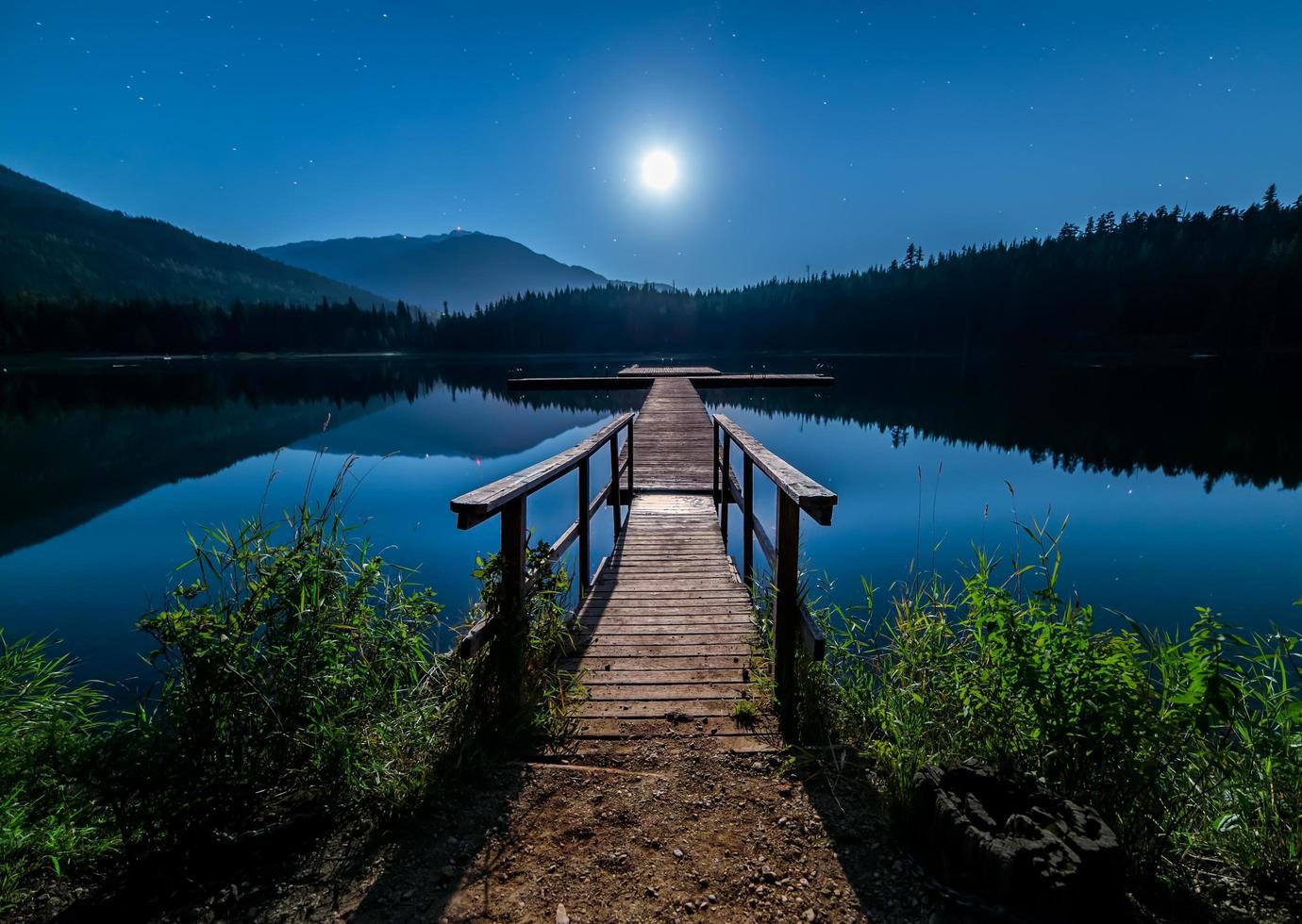 månbelyst brygga på vatten foto