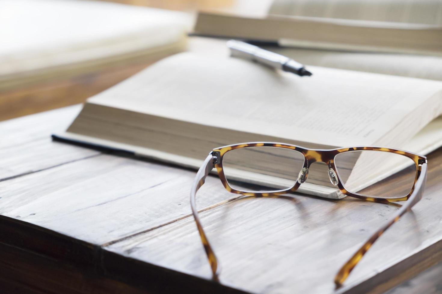 närbild av läsglasögon bredvid boken foto