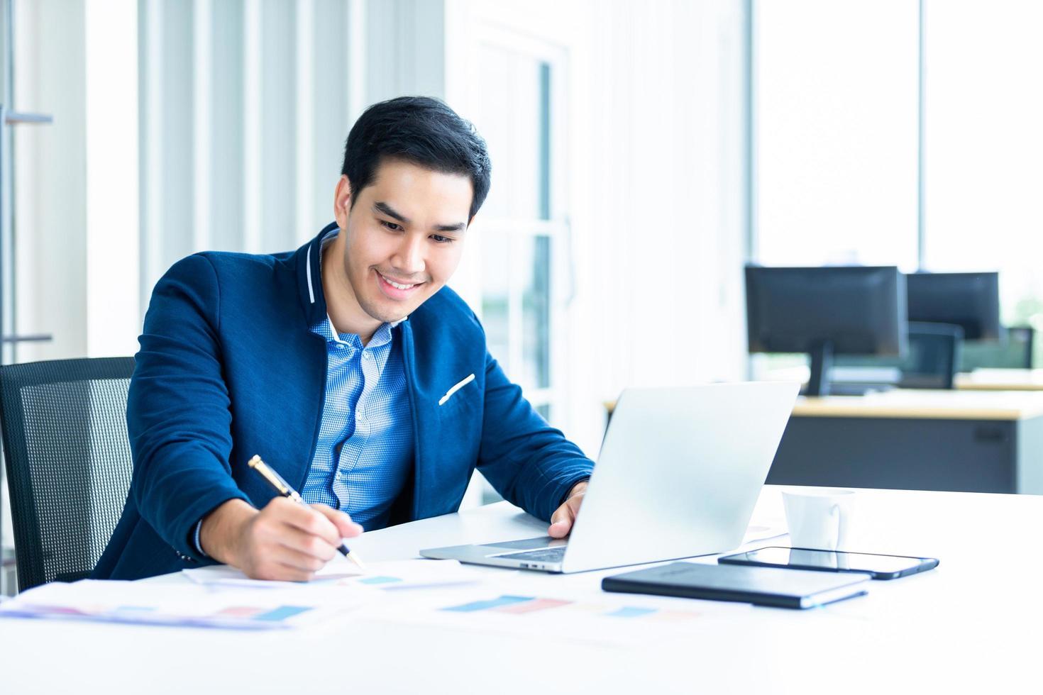 ung asiatisk affärsman som arbetar vid sitt skrivbord foto