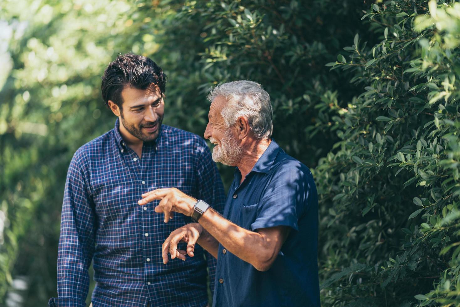 gammal far och vuxen son kopplar av i trädgården foto