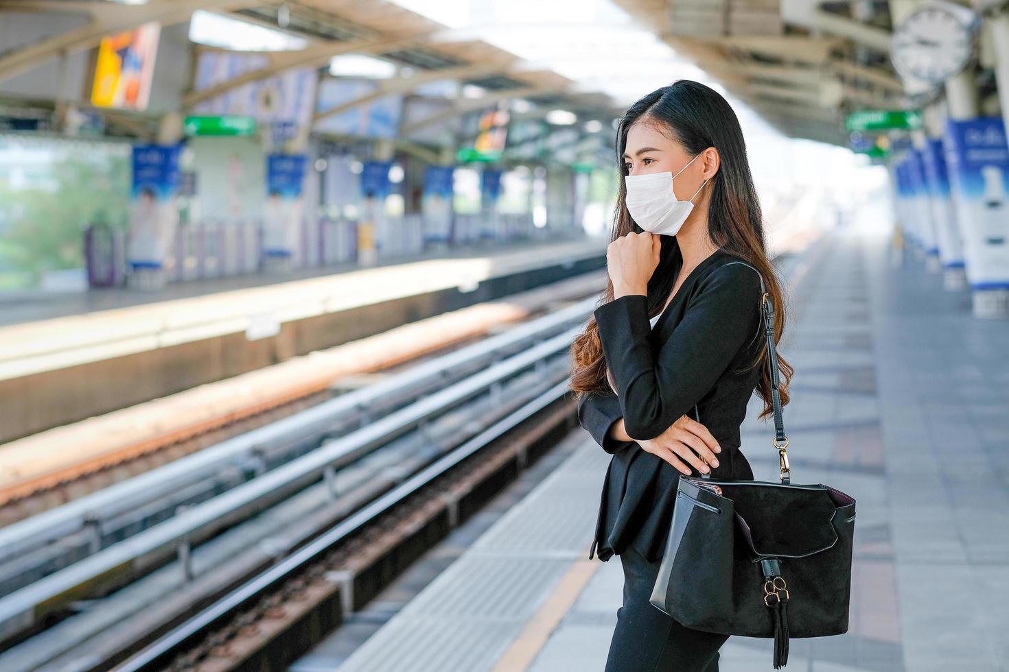 ung kvinna väntar på tåg foto