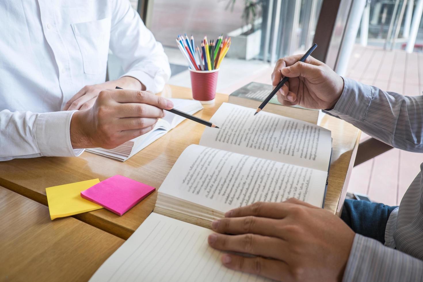 två personer som studerar och pekar på text i boken foto