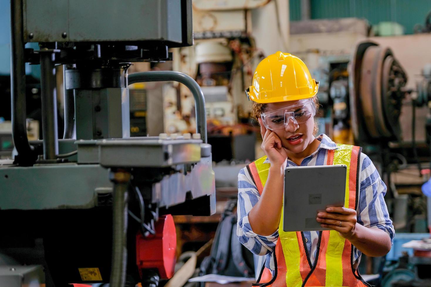 en kvinnlig maskinfabriksarbetare som slutför en inspektion foto