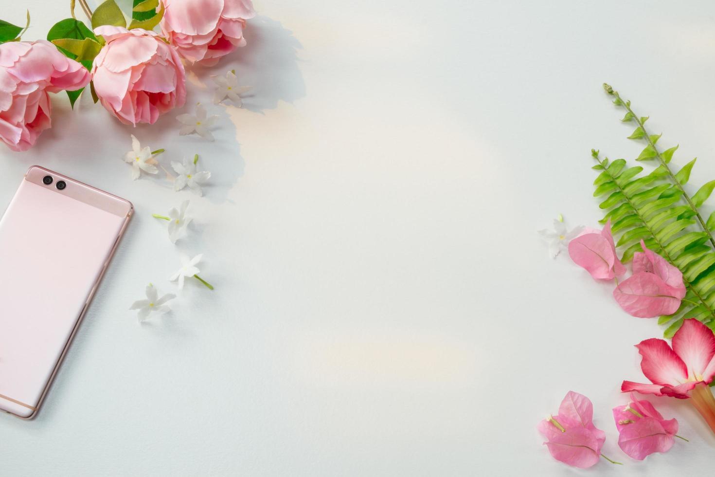 rosa blommor med ormbunkar och smartphone foto