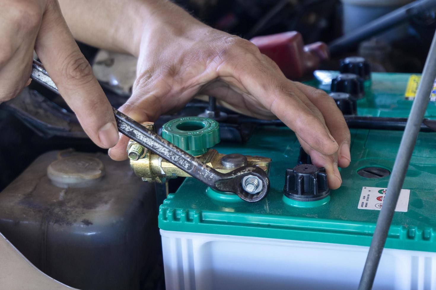 närbild av teknikerarbete på bilbatteri foto