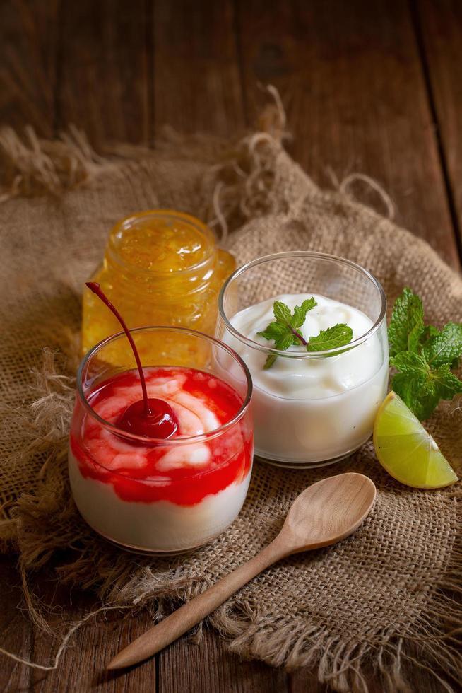 glas koppar yoghurt och frukt på texturerat tyg foto