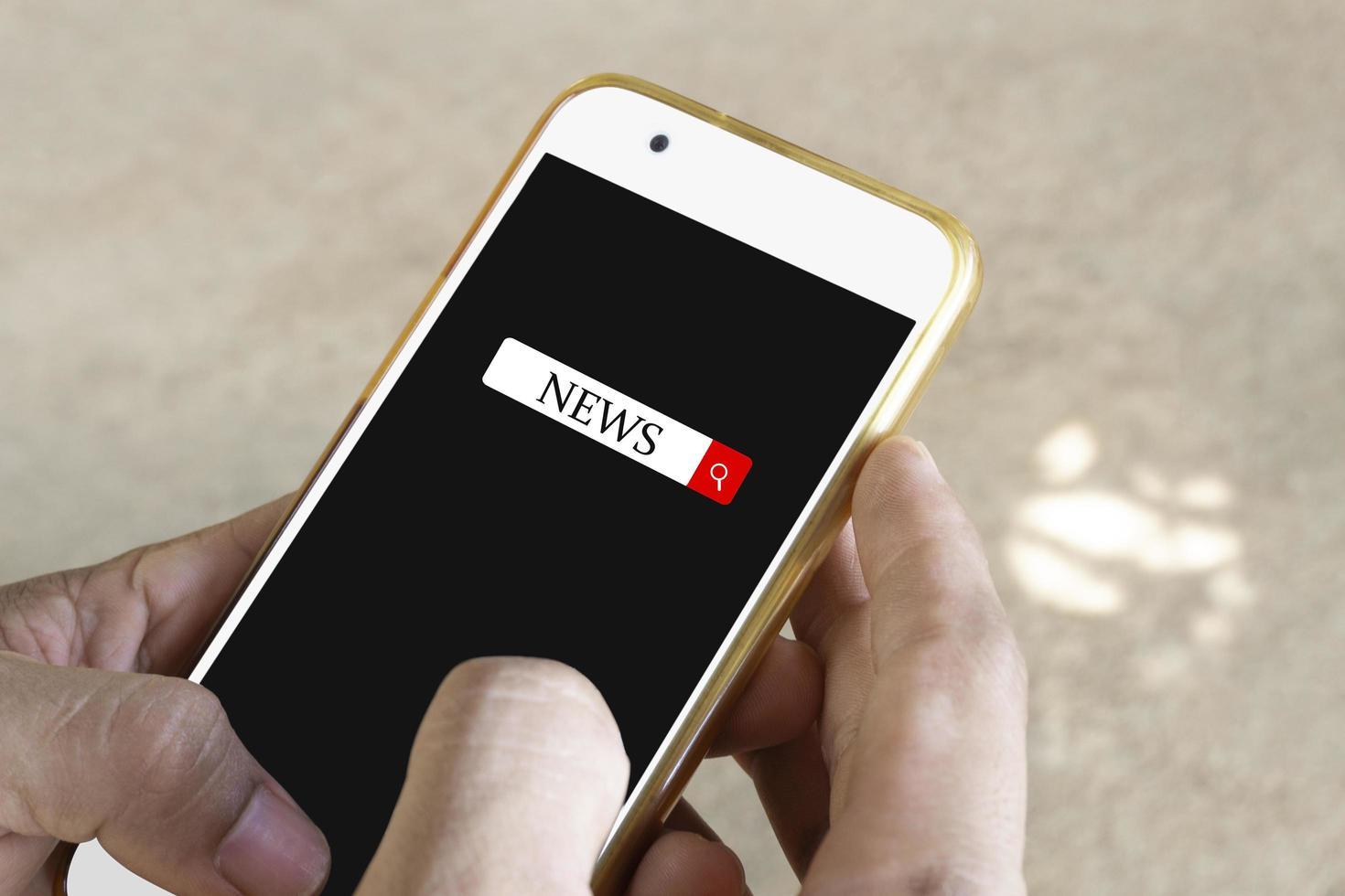 person som söker efter nyheter på smarttelefonen foto