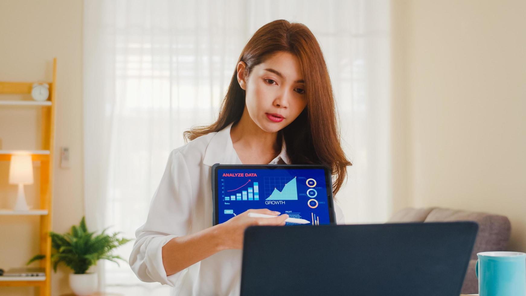 asiatisk affärskvinna som använder bärbar dator och surfplatta hemma foto