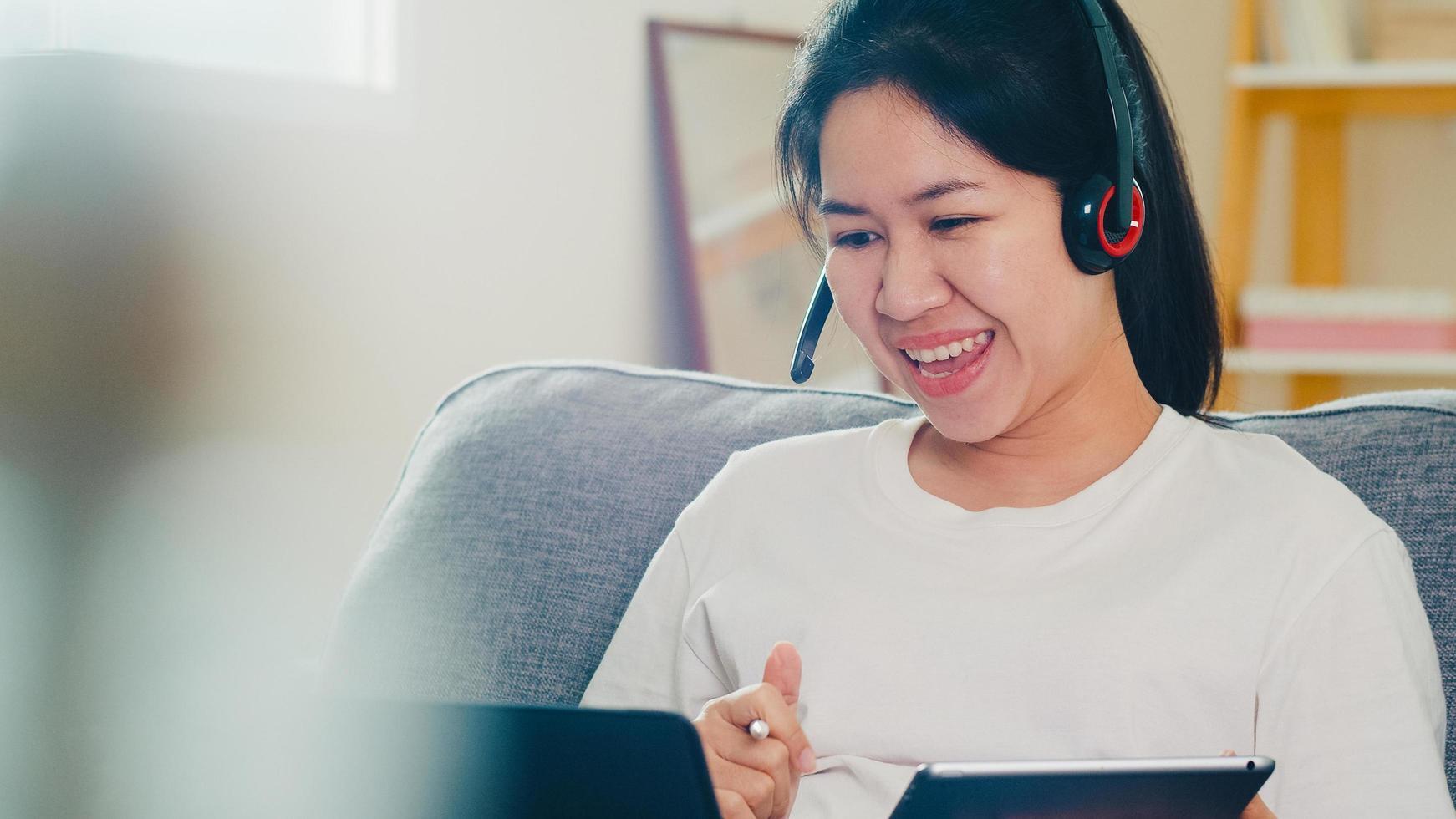 asiatisk frilansaffärskvinna som använder bärbara datorer hemma foto