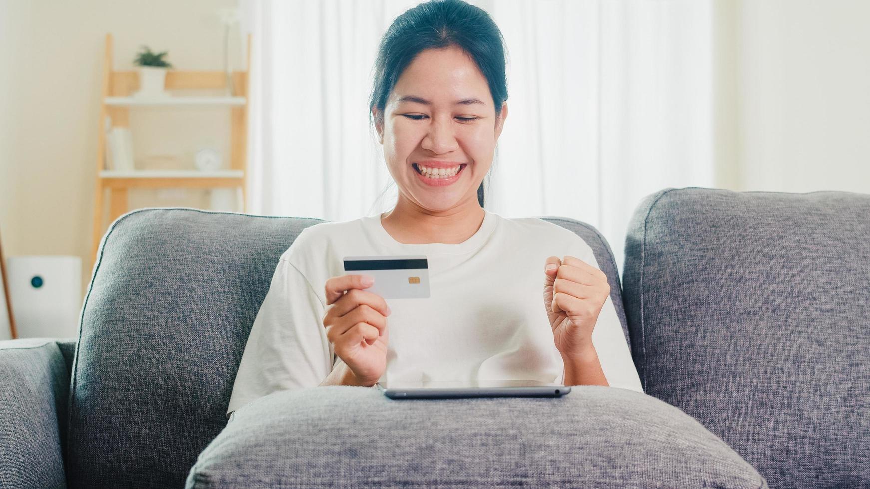 asiatisk kvinna som använder surfplatta och kreditkort i vardagsrummet. foto