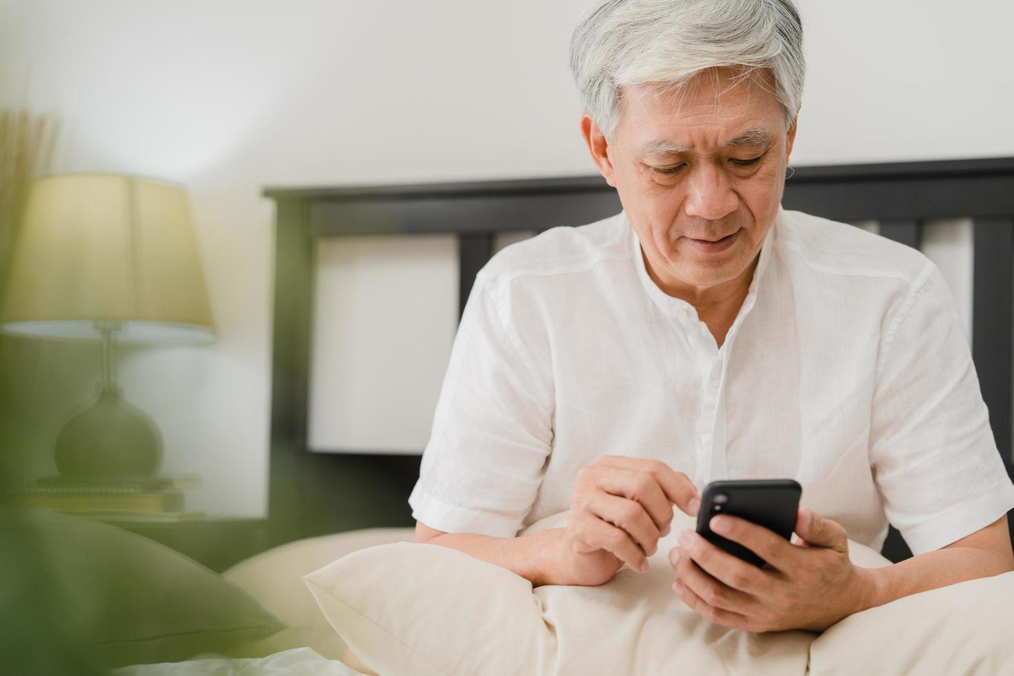 asiatisk äldre man som använder mobiltelefonen hemma foto