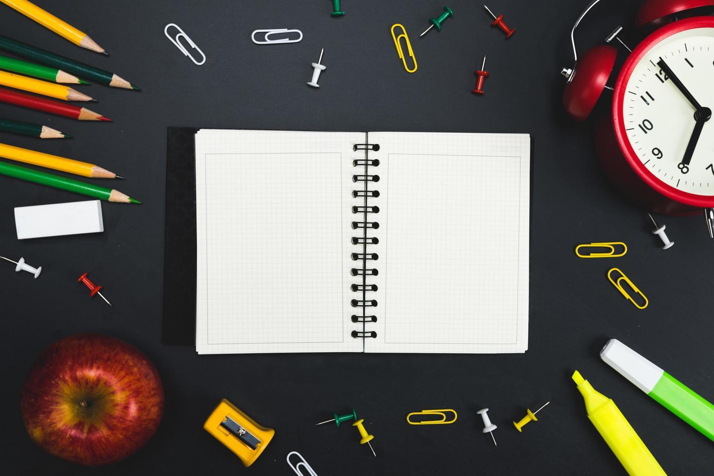 platt låg anteckningsbok omgiven av skolmaterial foto