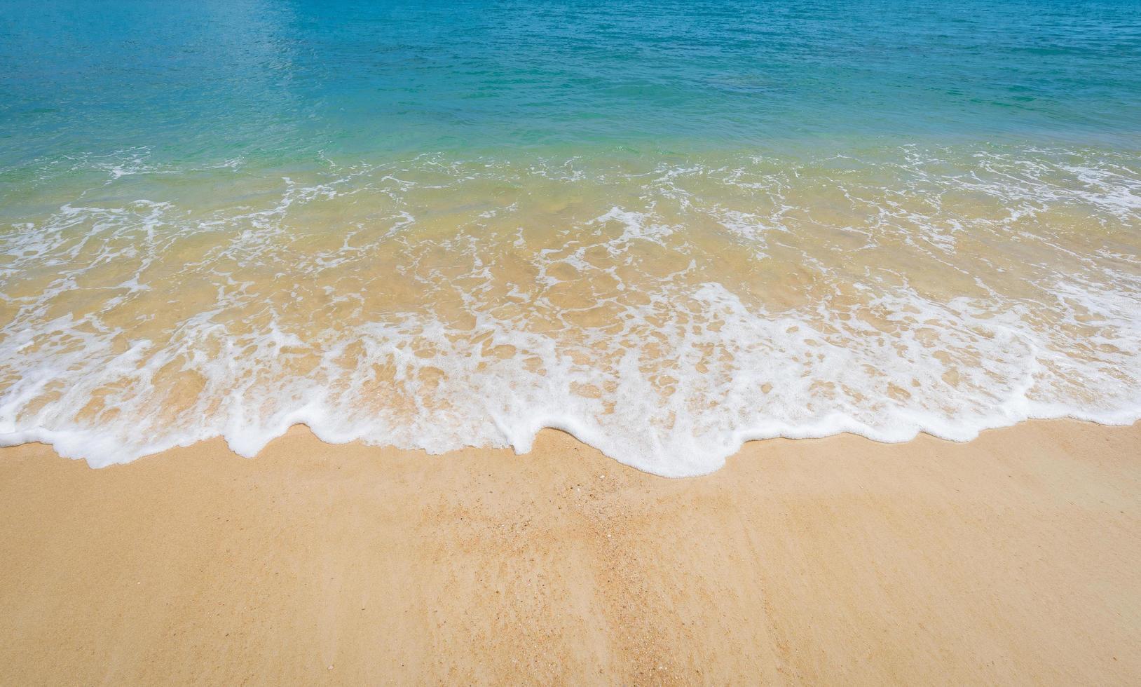 vågor tvättar upp på stranden foto
