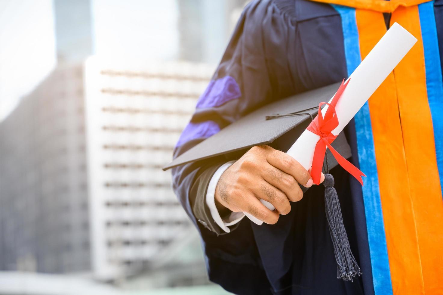 närbild av en examen som innehar examensbevis foto