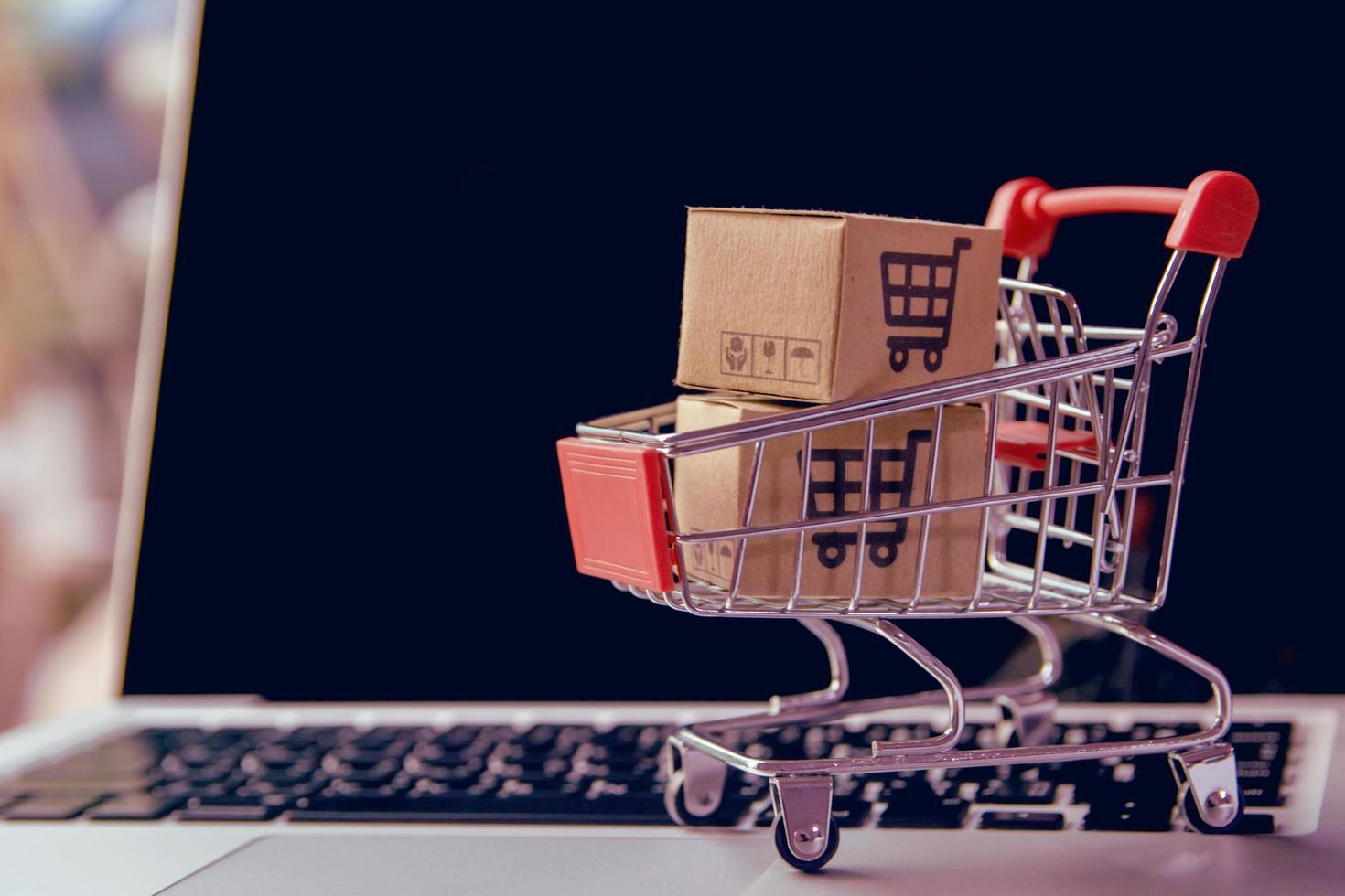 närbild av miniatyr kundvagn på bärbar dator foto