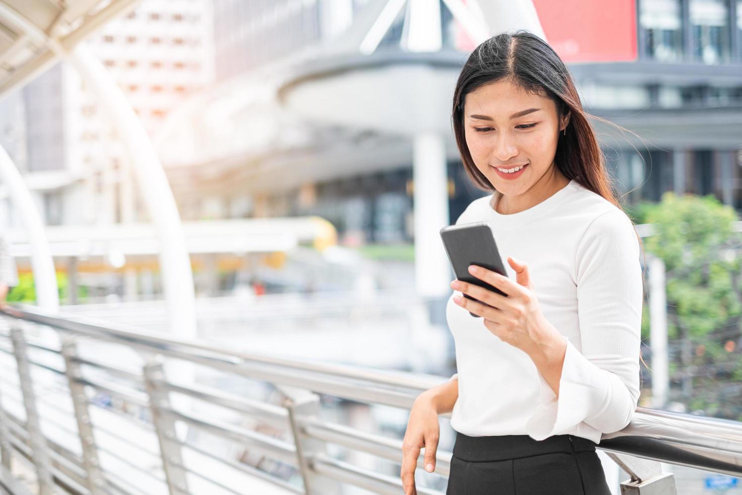 porträtt av asiatisk kvinna med smartphone foto