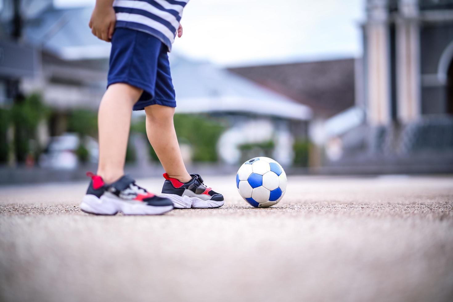 liten pojke med fotboll foto