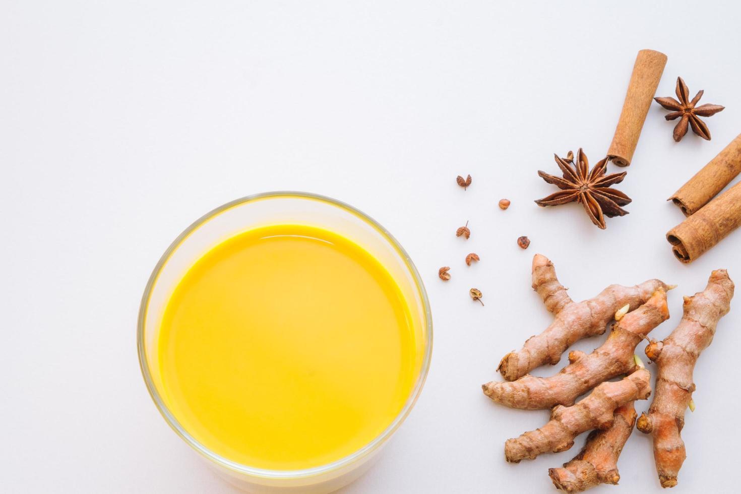 gyllene gurkmeja latte med kryddor på vit bakgrund foto