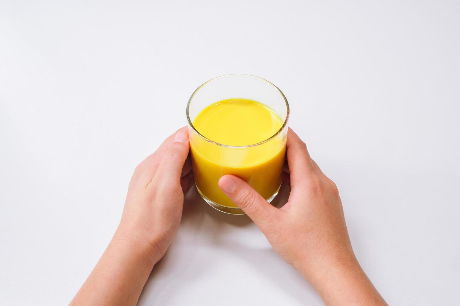 händer som håller ett glas gyllene mjölk gurkmeja latte foto