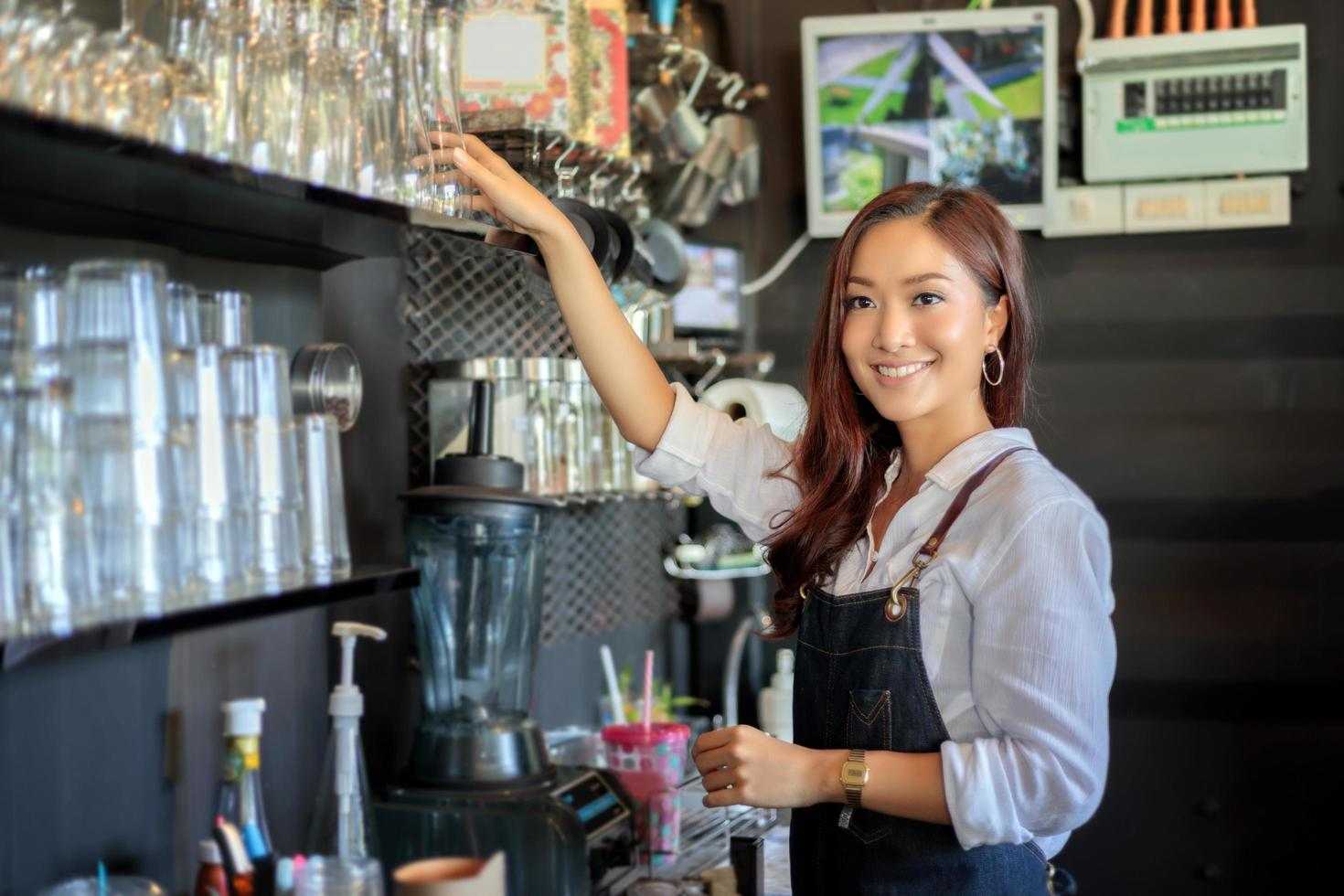 kvinnlig asiatisk barista leende medan du använder kaffemaskin foto