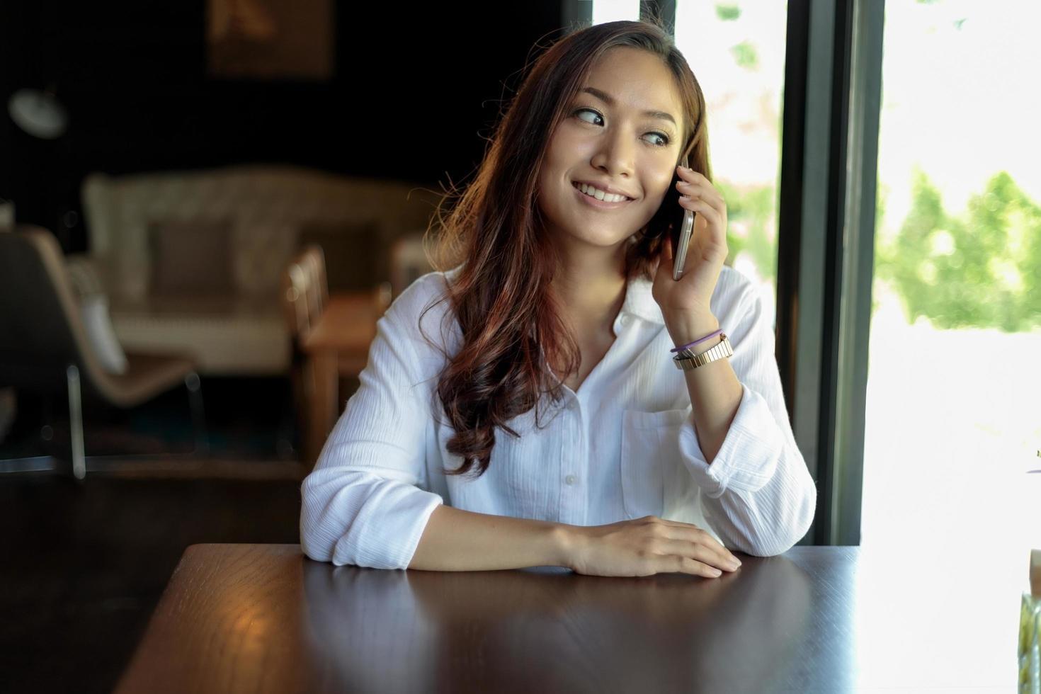ung asiatisk kvinna på kafé på telefon foto