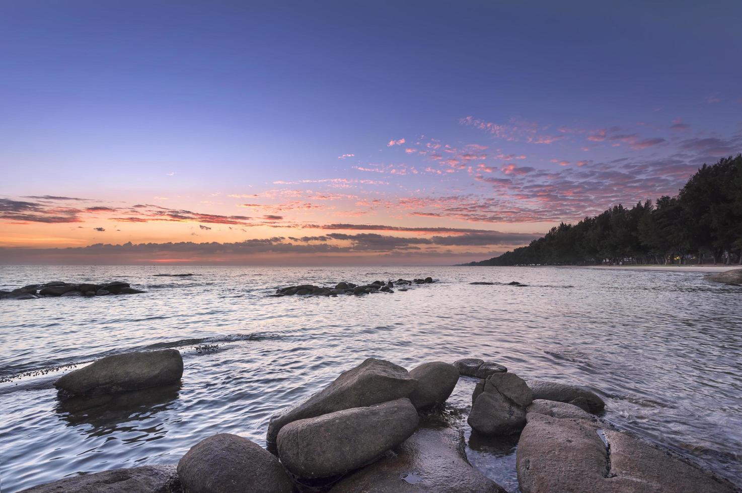 sten och seascape vid solnedgången tid foto