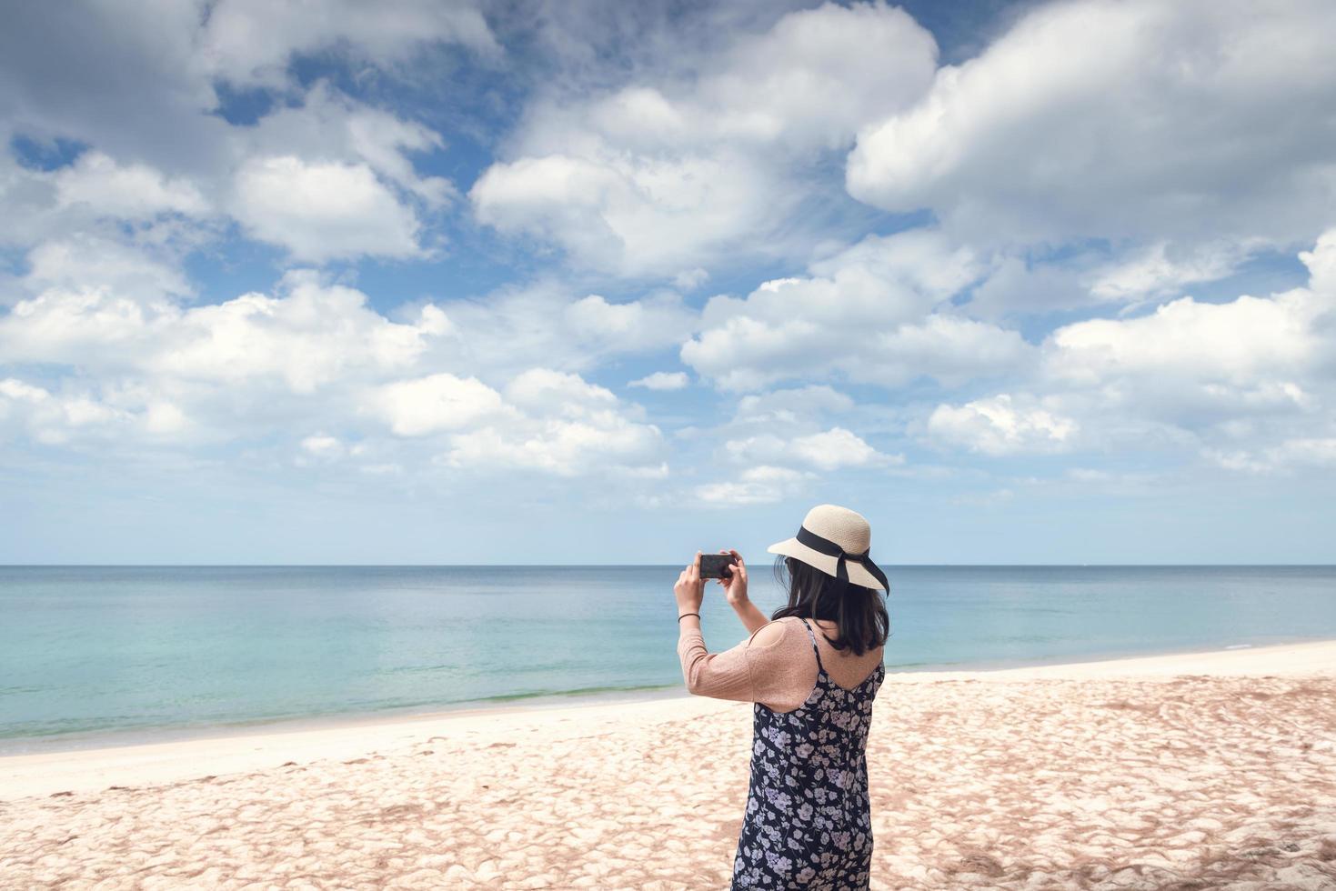 kvinna tar fotografi på stranden foto