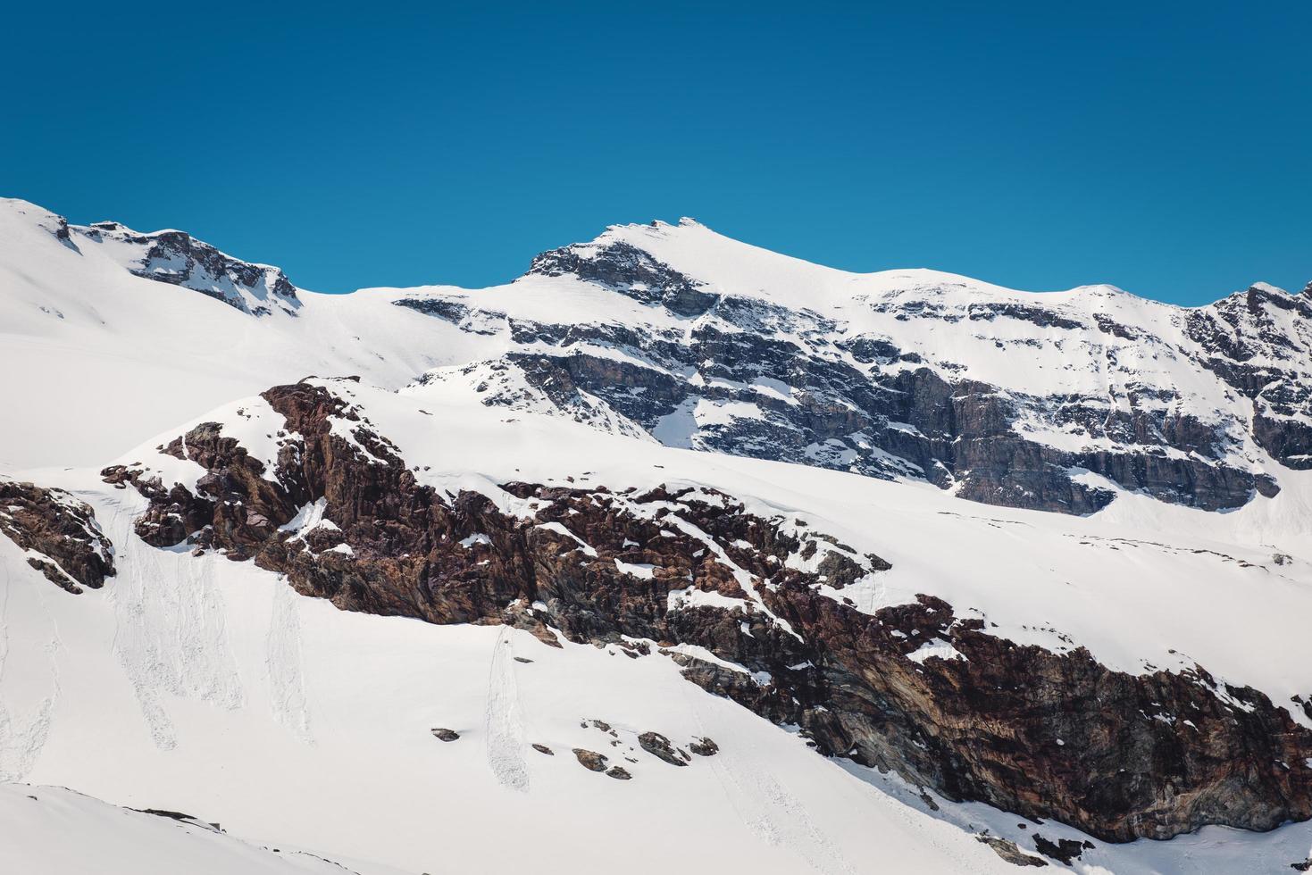 snöklädda berg och blå himmel foto